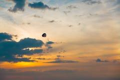 五颜六色的帆伞运动的跳伞运动员在sunriae/在se的日落 免版税库存照片