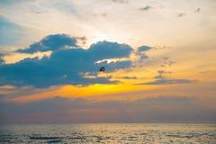 五颜六色的帆伞运动的跳伞运动员在sunriae/在se的日落 免版税库存图片