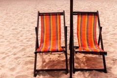五颜六色的床和伞在一个热带海滩 免版税库存图片