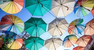 五颜六色的开放伞在尼科西亚,塞浦路斯盖街道 蓝天和遮阳伞背景的 免版税库存图片