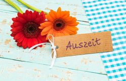 五颜六色的开花和卡片与德国词, Auszeit,手段放松或暂停 免版税库存图片