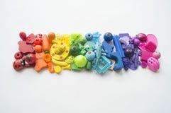 五颜六色的彩虹玩具熊行  许多个孩子玩具彩虹颜色 孩子在白色背景的玩具框架 顶视图 平的位置 免版税图库摄影