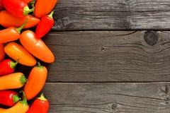 五颜六色的微型胡椒旁边边界在土气木头的 库存图片