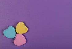 五颜六色的心脏。在紫色背景的三个甜心糖果 免版税库存照片