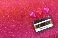 五颜六色的心脏形状巧克力和卡型盒式录音机的顶视图图象在红色闪烁背景 免版税库存照片