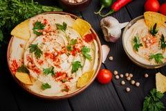 五颜六色的快餐构成的一张顶视图在黑木背景的 可口hummus在玻璃碗和在木 图库摄影