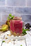 五颜六色的戒毒所夏天圆滑的人用红色莓果、梨、格兰诺拉麦片和干燥椰子立方体 库存图片