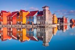五颜六色的房子临近木的水 免版税库存图片