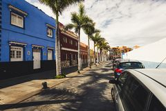 五颜六色的房子和棕榈树门面在典型的canarian街道,普埃尔托德拉克鲁斯,特内里费岛,西班牙上 免版税库存图片