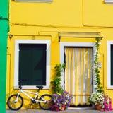 五颜六色的房子在有站立在花旁边的自行车的Burano 库存照片