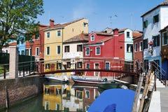 五颜六色的房子在运河在Burano,一个美丽的海岛明亮地反射了在威尼斯,意大利附近的威尼斯式盐水湖 库存图片