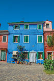 五颜六色的房子门面看法与灌木的在门旁边开花在Burano 库存图片