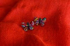 五颜六色的手工制造耳环,在红色织品背景 免版税图库摄影