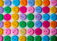 五颜六色的按钮行在白色桌背景的 免版税库存图片