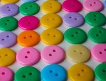 五颜六色的按钮行在白色背景的 免版税图库摄影