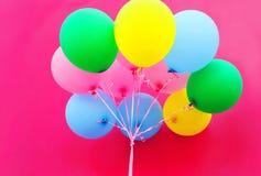 五颜六色的捆绑在桃红色背景特写镜头的气球 免版税库存图片