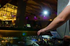 五颜六色的控制的看法在甲板的用DJ混合的音乐的手在音乐会的 库存图片