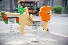 五颜六色的摇摆在孩子操场 被塑造的狮子和龙 库存图片