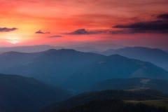 五颜六色的日落全景在山的 严重的阴暗天空 库存图片