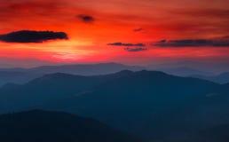 五颜六色的日落全景在山的 严重的阴暗天空 免版税库存图片