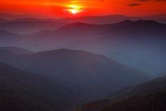 五颜六色的日落全景在山的 严重的阴暗天空 库存照片