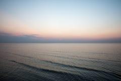 五颜六色的日落在有反射和云彩的海 免版税库存照片