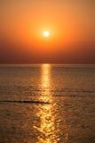 五颜六色的日落在有反射和云彩的海 库存图片