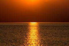 五颜六色的日落在有反射和云彩的海 免版税库存图片