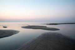 五颜六色的日落在有反射和云彩的海 免版税图库摄影