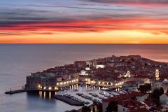 五颜六色的日落视图和月亮在杜布罗夫尼克,克罗地亚人历史的老镇  免版税库存图片