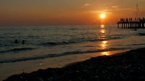 五颜六色的日落 与波浪的海视图和泡沫、码头和Pebble海滩 愉快的浮动人剪影在海 影视素材