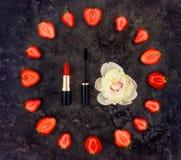 五颜六色的明亮的构成组成辅助部件、草莓和牡丹花 平的位置,顶视图 免版税库存照片