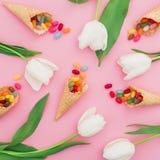 五颜六色的明亮的糖果的样式在奶蛋烘饼锥体和白花的在桃红色背景 平的位置,顶视图 免版税库存照片