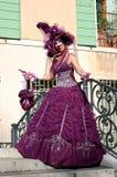 五颜六色的服装的美丽的在其中一座的妇女和面具威尼斯式桥梁 库存图片