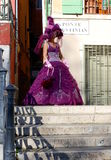 五颜六色的服装的美丽的在其中一座的妇女和面具威尼斯式桥梁 库存照片