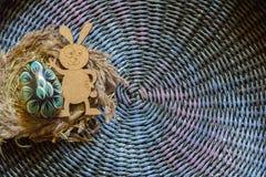 五颜六色的木复活节彩蛋和木屁股兔子在colorul背景 定调子 免版税库存照片