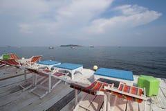五颜六色的木太阳海滩夏天椅子和桌在木 免版税库存照片