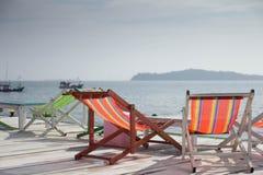 五颜六色的木太阳海滩夏天椅子和桌在木 库存照片