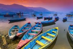 五颜六色的木小船停车处在Phewa湖和令人惊讶的日落在背景中 图库摄影
