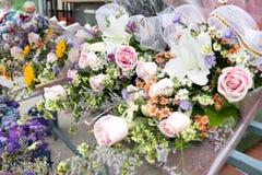 五颜六色的束桃红色玫瑰和白百合在出售的一个架子,曼谷,泰国开花 库存图片