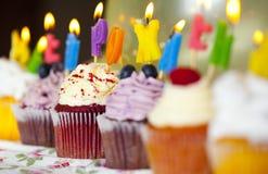 五颜六色的杯形蛋糕用与灼烧的蜡烛的奶油色和新鲜的莓果 免版税库存图片
