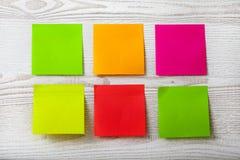 五颜六色的柱子纸笔记的汇集关于白色木背景的 免版税库存图片