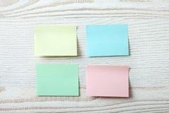 五颜六色的柱子纸笔记的汇集关于白色木背景的 免版税图库摄影