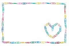 五颜六色的框架由纸夹制成在与心脏的白色背景同事的 库存图片