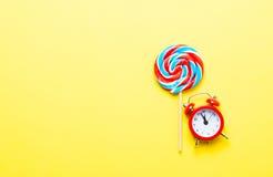 五颜六色的棒棒糖和闹钟 免版税库存照片