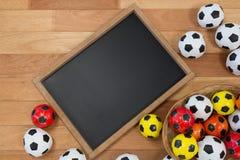 五颜六色的橄榄球和板岩在木桌上 免版税库存照片