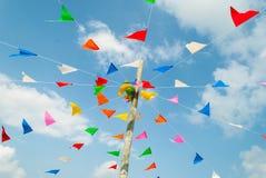 五颜六色的欢乐旗布旗子反对,在蓝色和云彩天空 免版税图库摄影