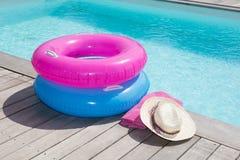 五颜六色的毛巾和蓝色和桃红色浮体在水池附近 免版税库存图片