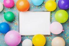 五颜六色的气球、银色框架和五彩纸屑在蓝色背景顶视图 计划的生日或党大模型 平的位置样式 库存照片