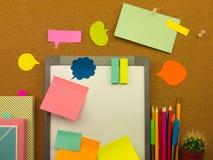 五颜六色的气球和笔记(黄柏板背景) 库存照片